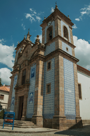 Gouveia, Portugal - July 17, 2018. Saint Peter Church facade covered by colorful ceramic tiles in a street of Gouveia. A nice country town with gardens and captivating historical heritage in Portugal.