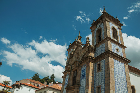 Pretty Saint Peter Church steeple in baroque style, covered by colorful ceramic tiles in a sunny day at Gouveia. A nice country town with gardens and captivating historical heritage in Portugal. Banco de Imagens - 124404124