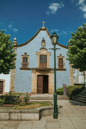 Gouveia, Portugal - July 17, 2018. Facade covered by ceramic tiles at the Church of the Misericordia of Gouveia. A nice country town with gardens and captivating historical heritage in Portugal. Banco de Imagens - 124404102