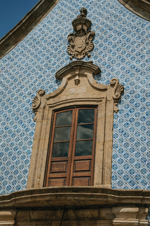 Window in baroque style with wall covered by colorful ceramic tiles, at the Church of the Misericordia of Gouveia. A nice country town with gardens and captivating historical heritage in Portugal. Banco de Imagens - 124404104
