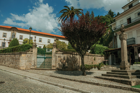 Deserted street with old buildings behind stone wall with iron gate and pillory, in a sunny day at Gouveia. A nice country town with gardens and captivating historical heritage in Portugal.