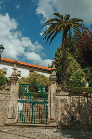 Stone wall with iron gate in front of old building and green trees from a garden, in a sunny day at Gouveia. A nice country town with gardens and captivating historical heritage in Portugal. Banco de Imagens - 124404106
