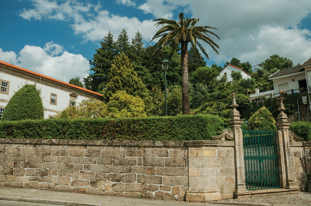 Stone wall with iron gate in front of old building and green trees from a garden, in a sunny day at Gouveia. A nice country town with gardens and captivating historical heritage in Portugal.