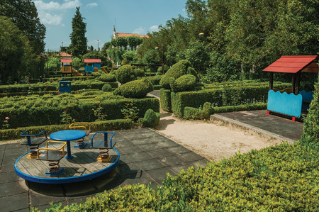 Leafy green bushes on a wooden garden with gravel pathway and playground, in a sunny day at Gouveia. A nice country town with gardens and captivating historical heritage in Portugal. Banco de Imagens - 124404078