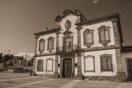 Mansion with exquisite stone decoration in baroque style on square at Lageosa do Mondego. A nice little village in the countryside, at mountain foothills on eastern Portugal. Black and white photo.