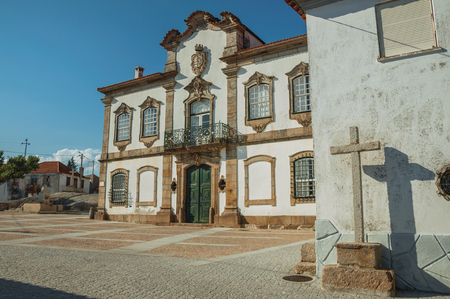 Mansion facade with charming decoration in baroque style on square and cross carved in stone at Lageosa do Mondego. A nice little village in the countryside, at mountain foothills on eastern Portugal.