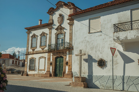 Mansion facade with charming decoration in baroque style on square and cross carved in stone at Lageosa do Mondego. A nice little village in the countryside, at mountain foothills on eastern Portugal. Banco de Imagens - 124404086