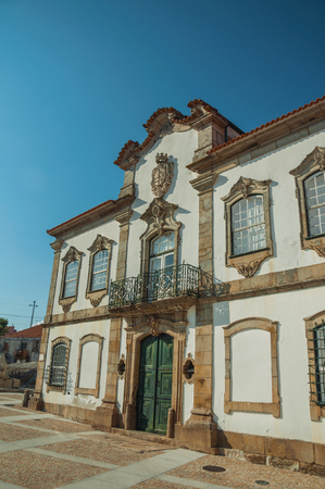 Mansion facade with exquisite stone decoration in baroque style on a deserted square at Lageosa do Mondego. A nice little village in the countryside, at mountain foothills on eastern Portugal. Banco de Imagens - 124404088