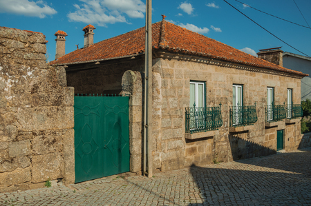 Lovely old house made of stone and wall with iron gate on deserted alley, in a sunny day at Lageosa do Mondego. A nice little village in the countryside, at mountain foothills on eastern Portugal. Archivio Fotografico
