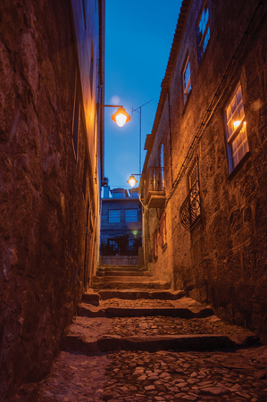 Narrow cobblestone alley with steps and old stone houses at nightfall with the lighting of public lamps at Guarda. This friendly and well-kept medieval town is the highest in the continental Portugal.