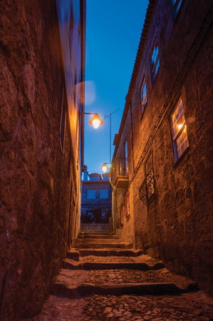 Narrow cobblestone alley with steps and old stone houses at nightfall with the lighting of public lamps at Guarda. This friendly and well-kept medieval town is the highest in the continental Portugal. Banco de Imagens - 124404046