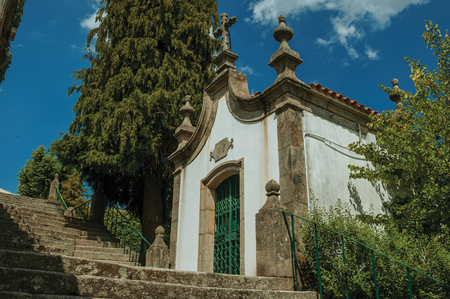 Small chapel finery decorated in baroque style next to stone staircase with green bushes, in a sunny day at Gouveia. A nice country town with gardens and captivating historical heritage in Portugal.