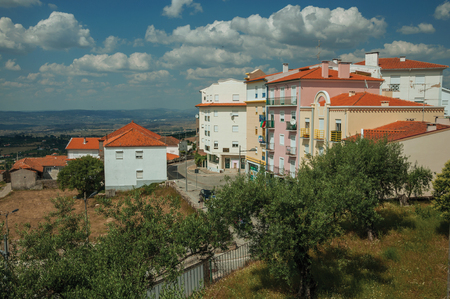 Colorful apartment buildings on hilltop with countryside landscape and trees, in a sunny day at Gouveia. A nice country town with gardens and captivating historical heritage in Portugal. Banco de Imagens - 124404059