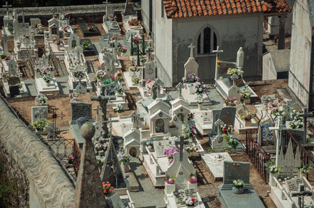 Gouveia, Portugal - July 17, 2018. Cemetery with crypts and marble tombs decorated by flowers at Gouveia. A nice country town with gardens and captivating historical heritage in Portugal. Banco de Imagens - 124404063