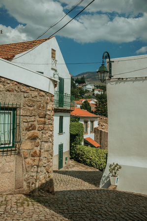 Facade of houses with stone and plaster wall on a narrow deserted alley, in a sunny day at Gouveia. A nice country town with gardens and captivating historical heritage in Portugal. Banco de Imagens - 124404064