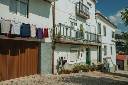 Gouveia, Portugal - July 17, 2018. Colorful clothes hung to dry in front of building with whitewashed wall in Gouveia. A nice country town with gardens and captivating historical heritage in Portugal. Banco de Imagens - 124404066