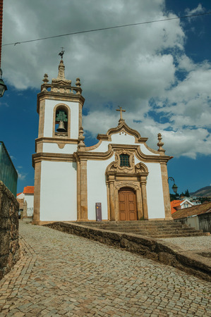 Gouveia, Portugal - July 17, 2018. Parish Church of Saint Julian facade in baroque style with steeple at Gouveia. A nice country town with gardens and captivating historical heritage in Portugal. Banco de Imagens - 124404024