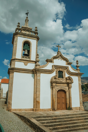 Parish Church of Saint Julian facade in baroque style with steeple and stone staircase, in a sunny day at Gouveia. A nice country town with gardens and captivating historical heritage in Portugal.