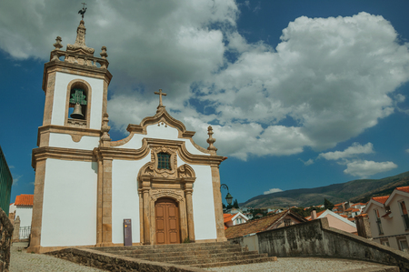 Gouveia, Portugal - July 17, 2018. Parish Church of Saint Julian facade in baroque style with steeple at Gouveia. A nice country town with gardens and captivating historical heritage in Portugal. Banco de Imagens - 124404026