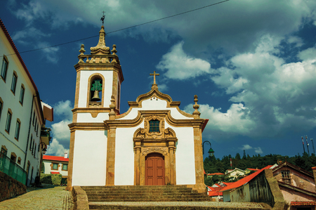 Parish Church of Saint Julian facade in baroque style with steeple and stone staircase at Gouveia. A nice country town with gardens and captivating historical heritage in Portugal. Retouched photo. Banco de Imagens - 124404031