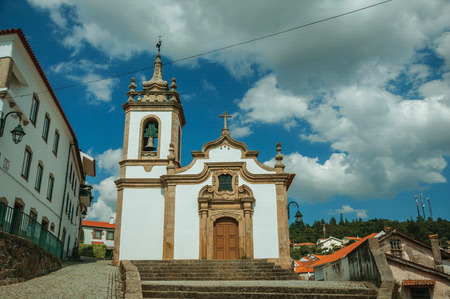 Parish Church of Saint Julian facade in baroque style with steeple and stone staircase, in a sunny day at Gouveia. A nice country town with gardens and captivating historical heritage in Portugal. Banco de Imagens - 124404032