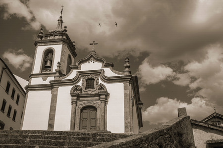 Parish Church of Saint Julian in baroque style with steeple and stone staircase at Gouveia. A nice country town with gardens and captivating historical heritage in Portugal. Black and white photo.