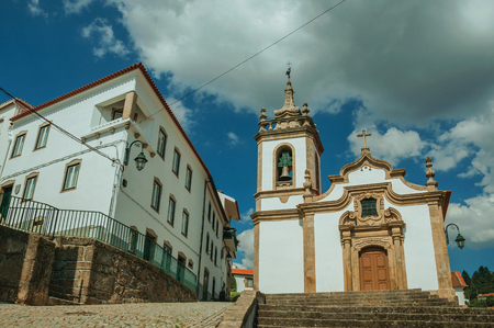 Parish Church of Saint Julian facade in baroque style with steeple and stone staircase, in a sunny day at Gouveia. A nice country town with gardens and captivating historical heritage in Portugal. Banco de Imagens - 124404034