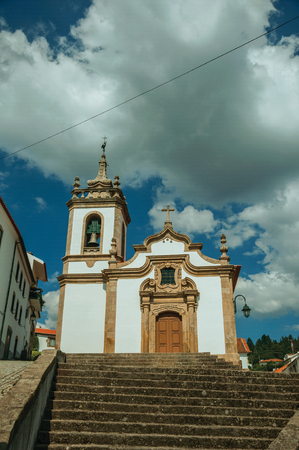 Parish Church of Saint Julian facade in baroque style with steeple and stone staircase, in a sunny day at Gouveia. A nice country town with gardens and captivating historical heritage in Portugal. Banco de Imagens - 124404037
