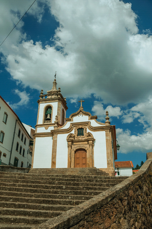 Parish Church of Saint Julian facade in baroque style with steeple and stone staircase, in a sunny day at Gouveia. A nice country town with gardens and captivating historical heritage in Portugal. Banco de Imagens - 124404038
