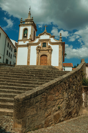 Parish Church of Saint Julian facade in baroque style with steeple and stone staircase, in a sunny day at Gouveia. A nice country town with gardens and captivating historical heritage in Portugal. Banco de Imagens - 124404039