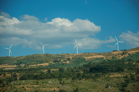 Some wind turbines for electric power generation on green hilly landscape with rocks, in a sunny day at Serra da Estrela. The highest mountain range in continental Portugal, with astonishing scenery. Banco de Imagens - 124404040
