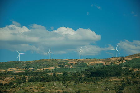 Some wind turbines for electric power generation on green hilly landscape with rocks, in a sunny day at Serra da Estrela. The highest mountain range in continental Portugal, with astonishing scenery. Banco de Imagens - 124404041
