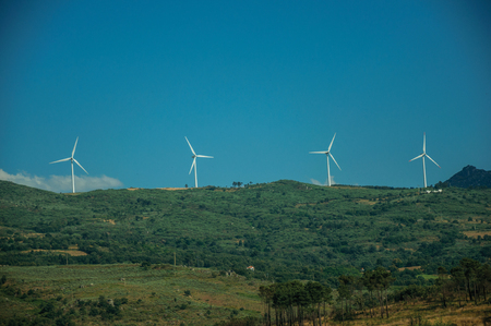 Some wind turbines for electric power generation on green hilly landscape with rocks, in a sunny day at Serra da Estrela. The highest mountain range in continental Portugal, with astonishing scenery. Banco de Imagens