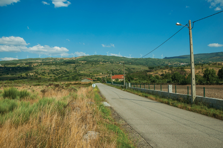 Countryside paved road passing through hilly landscape with farms and dry bushes, in a sunny day at Serra da Estrela. The highest mountain range in continental Portugal, with astonishing scenery. Banco de Imagens - 124404043