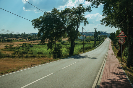 Close-up of straight road passing through countryside landscape with trees and brick sidewalk, at Serra da Estrela. The highest mountain range in continental Portugal, with astonishing scenery. Banco de Imagens - 124404044