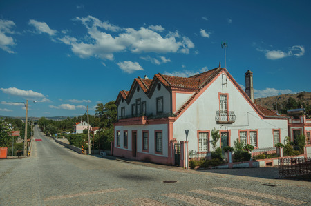 Pretty two-story house next to a road passing through countryside landscape, in a sunny day at Lageosa do Mondego. A nice little village in the countryside, at mountain foothills on eastern Portugal.