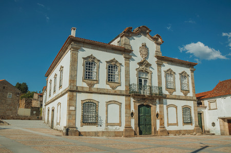 Mansion facade with exquisite stone decoration in baroque style on a deserted square at Lageosa do Mondego. A nice little village in the countryside, at mountain foothills on eastern Portugal. Banco de Imagens - 124403954