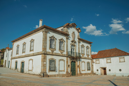 Mansion facade with exquisite stone decoration in baroque style on a deserted square at Lageosa do Mondego. A nice little village in the countryside, at mountain foothills on eastern Portugal. Banco de Imagens - 124403955