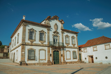 Mansion facade with exquisite stone decoration in baroque style on a deserted square at Lageosa do Mondego. A nice little village in the countryside, at mountain foothills on eastern Portugal. Banco de Imagens