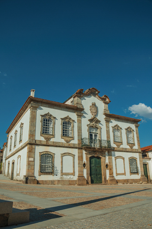 Mansion facade with exquisite stone decoration in baroque style on a deserted square at Lageosa do Mondego. A nice little village in the countryside, at mountain foothills on eastern Portugal. Banco de Imagens - 124403957