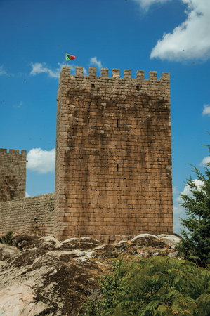 Stone towers with flag and long wall over rocky hill, in a sunny day at the Linhares da Beira Castle. A medieval hamlet with unique architectural diversity fruit of several times, in eastern Portugal.