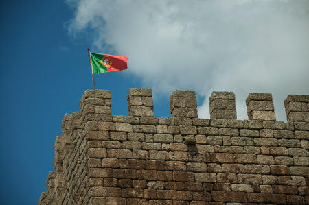 Portuguese flag fluttering on top of stone tower, in a sunny day at the Linhares da Beira Castle. A medieval hamlet with unique architectural diversity fruit of several times, in eastern Portugal.