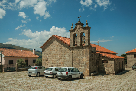 Linhares da Beira, Portugal - July 17, 2018. Stone church and bells on a square with cars at Linhares da Beira. A medieval hamlet with unique architectural diversity in eastern Portugal.