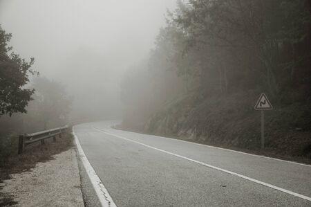 Carretera que atraviesa un paisaje de madera cubierto por la niebla en las tierras altas de la Serra da Estrela. La cadena montañosa más alta de Portugal continental, con un paisaje asombroso. Fotografía en blanco y negro. Foto de archivo