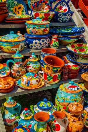 Colorful handmade porcelain pots and dishes typical of the region, on gift shop at the Serra da Estrela. The highest mountain range in continental Portugal, with astonishing scenery. Retouched photo.