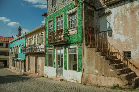 Old houses with worn facade and staircase with rusty railing on deserted alley, in a sunny day at Belmonte. A cute small town, birthplace of the navigator Pedro Alvares Cabral, on eastern Portugal. Imagens