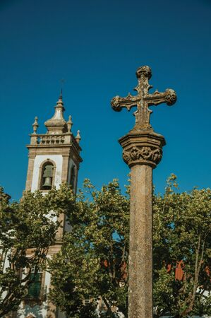 Baroque bell tower from Church of the Misericordia and stone pillory with cross on top, in a sunny day at Guarda. This friendly and well-kept medieval town is the highest in the continental Portugal.
