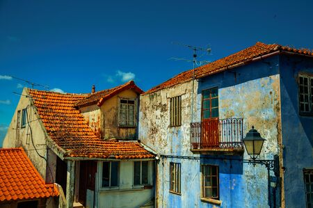 Old colorful houses with worn plaster in a sunny day at Seia. On foothill mountains, this friendly town in eastern Portugal is also known for its delicious artisanal cheese. Retouched photo.