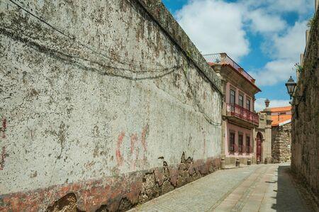 Schmale Gasse mit abgenutzter Gipswand und altem buntem Haus, an einem sonnigen Tag in Seia. Diese freundliche Stadt im Osten Portugals am Fuße der Berge ist auch für ihren köstlichen handwerklichen Käse bekannt. Standard-Bild