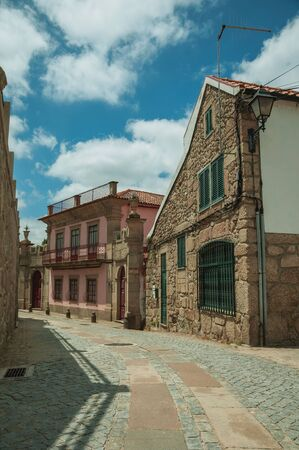 Old house with stone wall on corner of deserted alley, in a sunny day at Seia. On foothill mountains, this friendly town in eastern Portugal is also known for its delicious artisanal cheese.